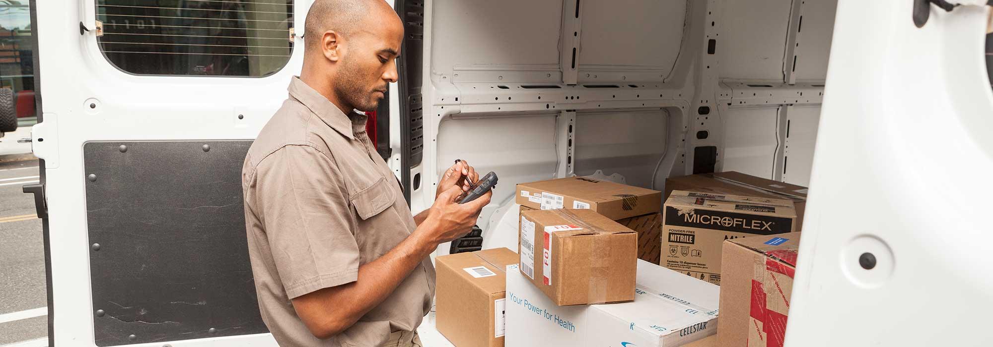 En mann som taster på en telefon stående ved en varebil