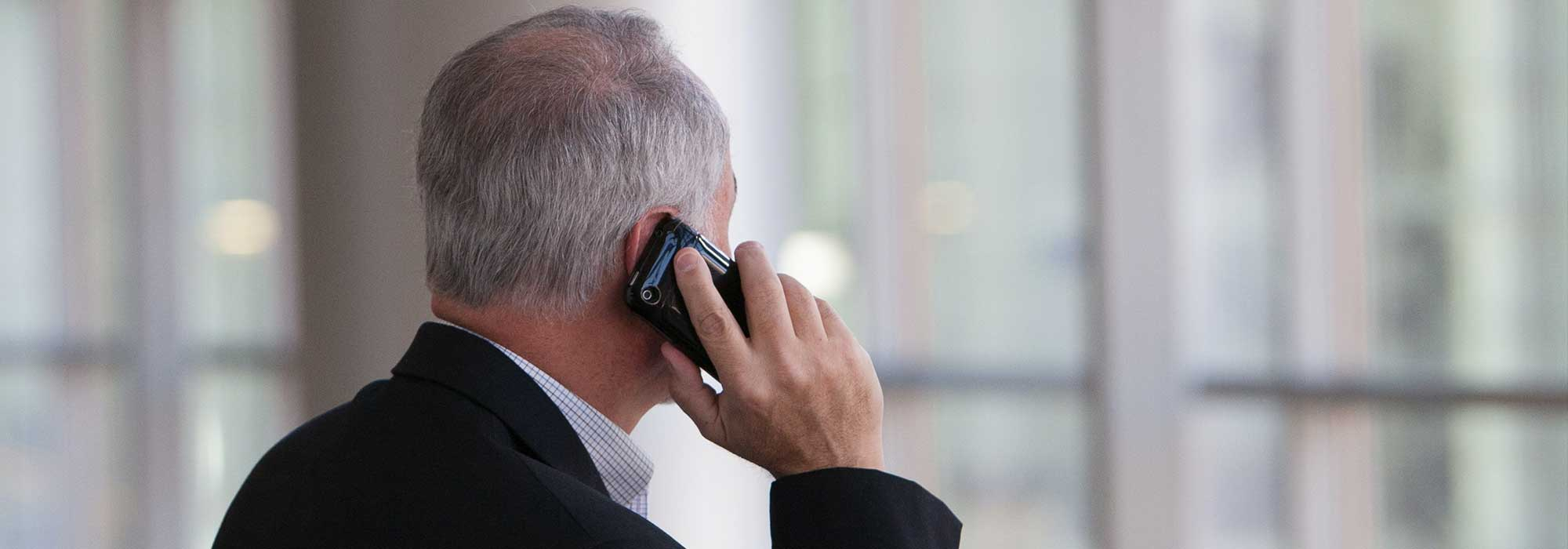 En mann som prater i telefon stående med ryggen til