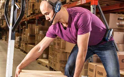 En mann som løfter en eske på et lager med lagersystem på montert på øret