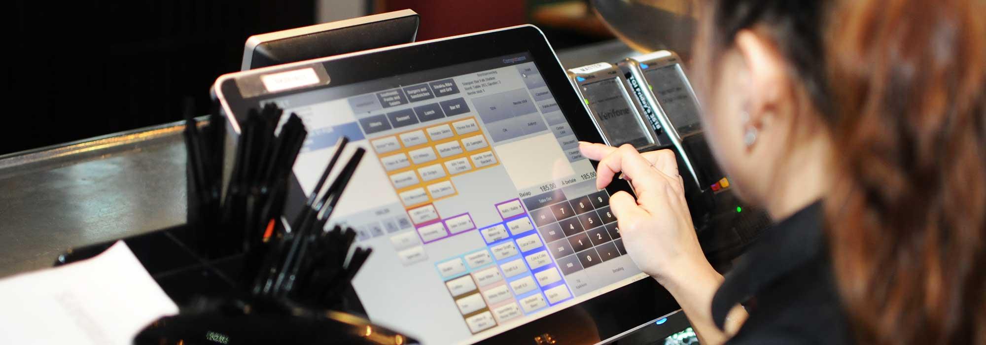 En ansatt trykker på en dataskjerm i en restaurant