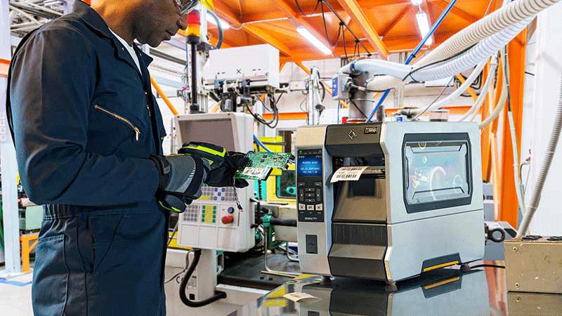 Industriarbeider med skanner står ved en printer og annet utstyr