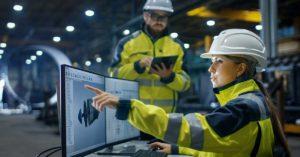 to industriarbeidere foran pc-skjerm og nettbrett